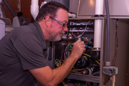 Furnace Tech Taking A Part Off A Gas Furnace Stock Photo - 141607158