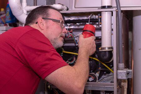 HVAC Tech Inspecting A Gas Furnace Stock Photo