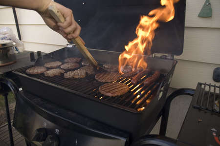 Hamburgers and hot dogs cooking on barbeque grill with flames. Stock Photo - 704038