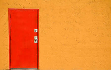 stucco: Red steel door in a stucco wall.