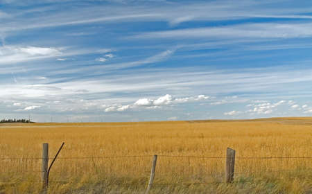 Wolken tegen de blauwe hemel boven boeren veld met prikkeldraad afrastering.