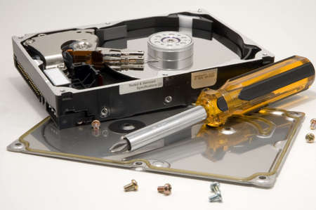 hard: A disassembled hard drive with a screwdriver. Stock Photo