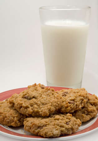 Havermout chocolade chip cookies op een plaat met een groot glas melk.