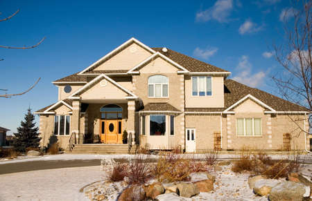A two-story brick luxury home with a rock garden. Stock Photo