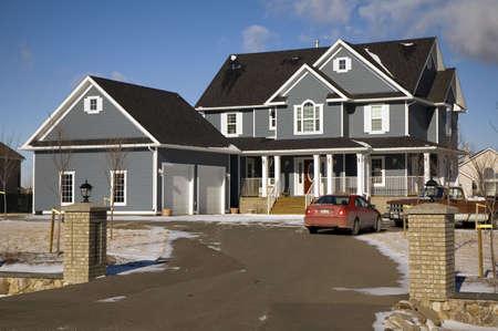 Een blauw luxe huis met een dubbele garage en een dek.