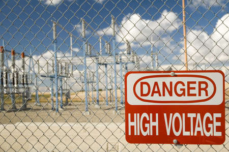 Electrical substation with 'High Voltage' sign.