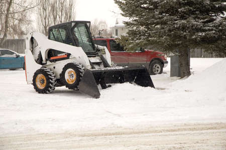 Bobcat removing snow in a parking lot.