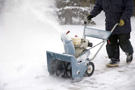 Man removing snow with a snow blower. Stock Photo