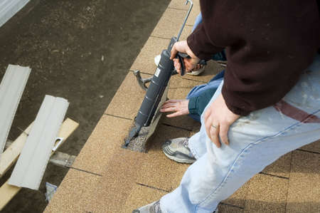 Roofing: Applying tar under shingles.