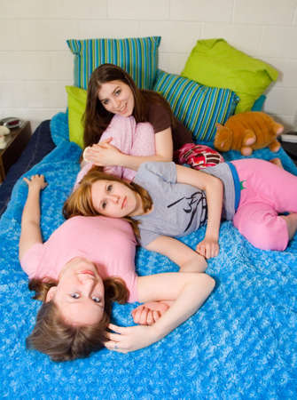 slumber: Young women wearing pink pajamas on a fuzzy blue blanket.