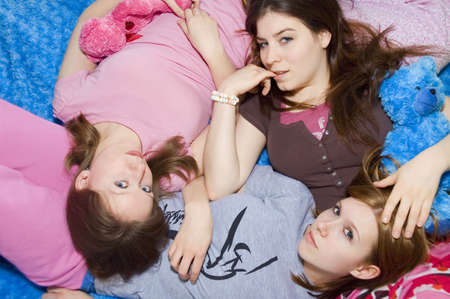 slumber: 3 girls laying on each other in their pajamas.