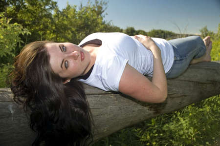 log hair: Woman with long hair laying on a log.