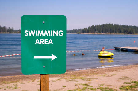 Green swimming area direction sign.