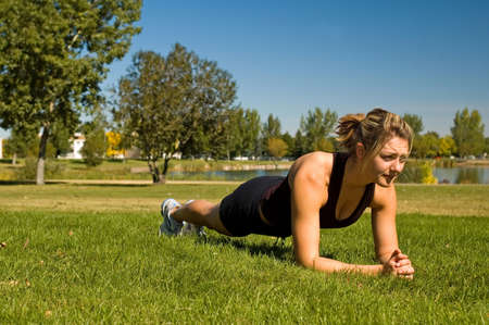 Fit young woman doing the Plank exercise.