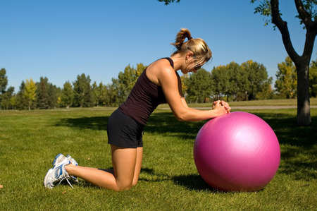Jonge vrouw het uitvoeren van een ab roll, met een excersize bal. Stockfoto