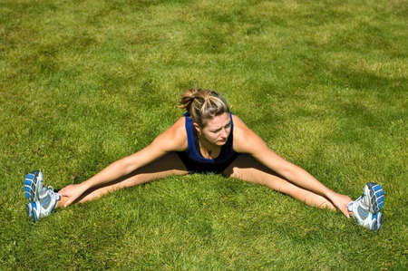 hamstrings: Woman in black shorts stretching her groin muscles.