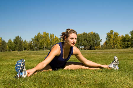 Woman in black shorts stretching her groin muscles.