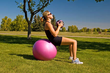 Young woman doing a situp on an exercise ball with a 4 lbs weight. Stock Photo