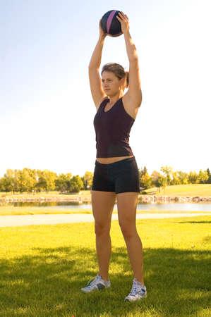 Junge Frau in einem Park machen Übungen mit einem 4-Pfund-Ball.