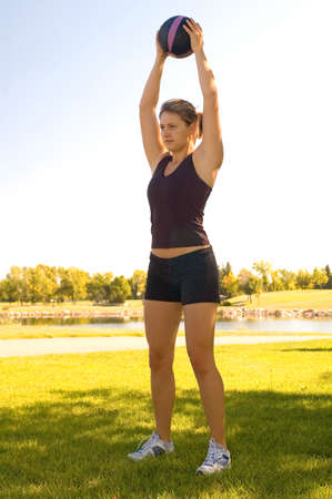 hottie: Young woman in a park doing exercises with a 4 pound ball. Stock Photo