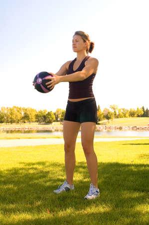 Jonge vrouw in een park doet oefeningen met een 4 pond bal.