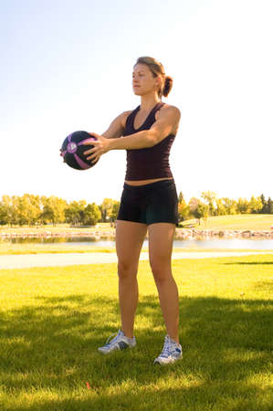 Young woman in a park doing exercises with a 4 pound ball. Stock Photo
