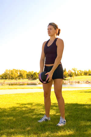 Young woman in a park doing exercises with a 4 pound ball. Stock Photo - 1729295