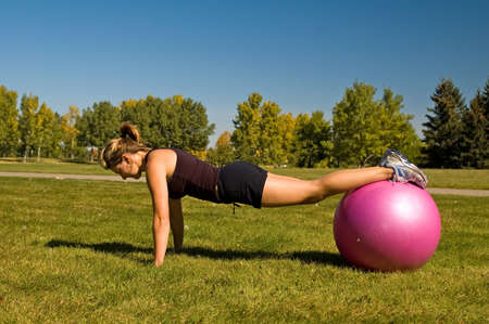 Young woman doing push ups with an exercise ball.