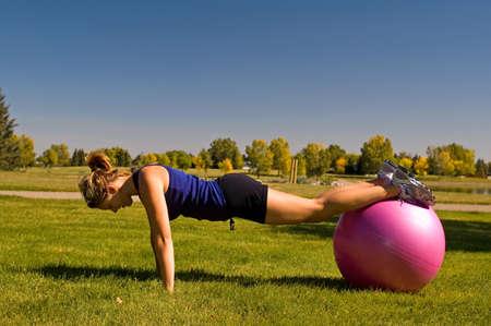 Jonge vrouw doet push ups met een oefening bal. Stockfoto