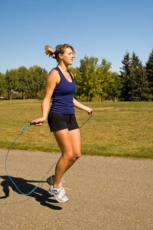 hottie: Young woman using a jump rope in a park.