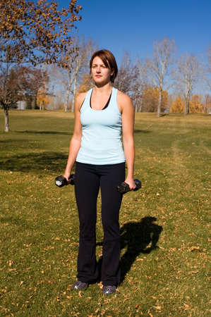 curls: Young woman performing bicep curls. Stock Photo
