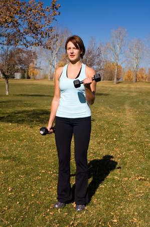 Young woman performing bicep curls. photo