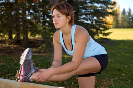 hamstrings: Young woman bending over to stretch her hamstrings. Stock Photo