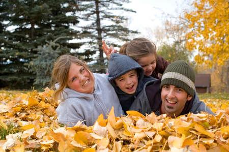 Jonge vader en een stel kinderen plezier hebben in sommige bladeren.
