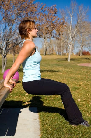 dip: Young woman performing tricep dips on a bench. Stock Photo