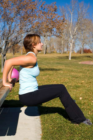 tricep: Young woman performing tricep dips on a bench. Stock Photo