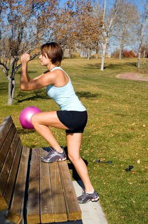 Jonge vrouw doet stap ups bankje in een park. Stockfoto