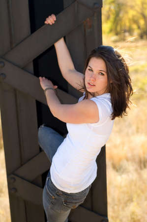 jeans apretados: Joven mujer colgando de un puente.