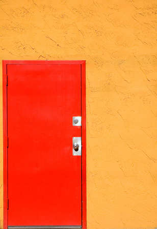 Red steel door in an orange stucco wall. Stock fotó