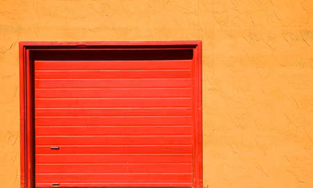 Red steel garage door in an orange stucco wall.