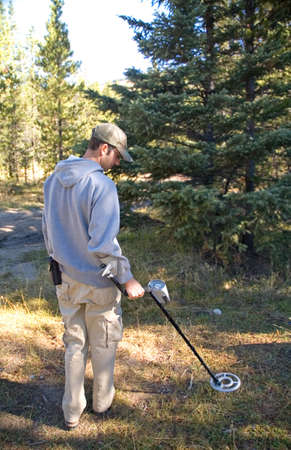 Mens die met een metaaldetector in het bos onderzoekt.