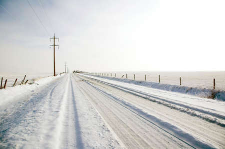 Winter covers a rural farm access road. photo