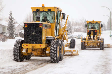 grader: Two city plows clearing snow from the streets. Stock Photo