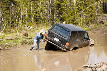 attaching: 4x4 vehicle stuck in a mud hole, with a man attaching a winch. Stock Photo
