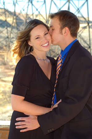 hottie: Young man kissing his fiance on the cheek. Stock Photo