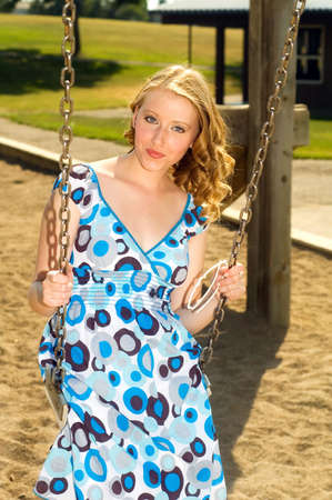 Pretty blonde sitting in a swing, at a playground. photo