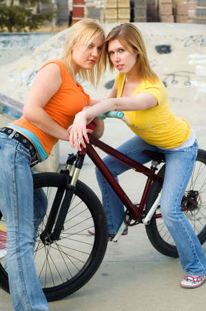 sisters sexy: Attractive women posing on a bike. Stock Photo