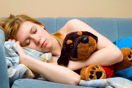 taking nap: Young woman taking a nap with a stuffed animal.