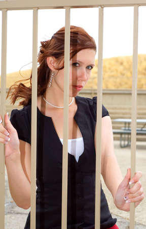 trapped: Attractive young woman trapped behind bars. Stock Photo
