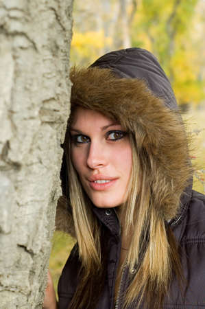 Autumn girl leaning against a tree, wearing a black coat with the hood up.